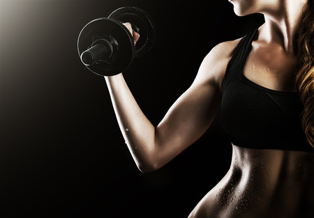 Dark contrast photo of muscular arms, waist and belly with beads of sweat of young fitness woman, which training, working out with dumbbells on black background