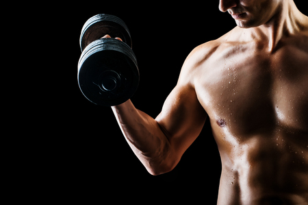 fit: Focus on stomach. Dark contrast shot of young muscular fitness man stomach and arm.  Stock Photo