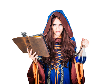 spells: Beautiful young halloween witch wearing vintage gothic dress with hood reading magical book of spells in old leather cover and holding potion in glass flask