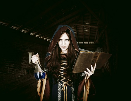 spells: Beautiful young halloween witch wearing vintage gothic dress with hood reading magical book of spells in old leather cover and holding potion in night castle Stock Photo