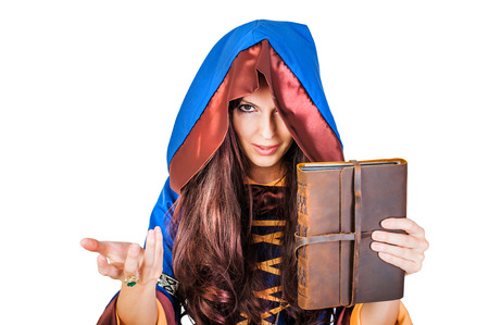spells: Beautiful young halloween witch wearing vintage gothic dress with hood holding magical book of spells in old leather cover isolated on white background Stock Photo