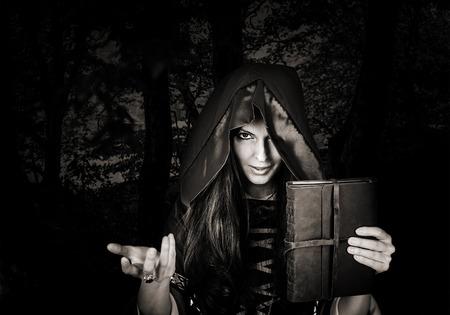 Mooie jonge Halloween heks dragen van vintage gothic jurk met capuchon met magische boek spreuken in het oude lederen cover in donkere nacht bos