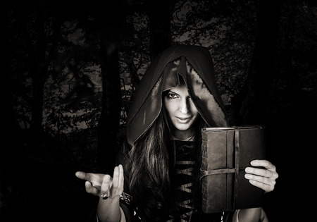 Beautiful young halloween witch wearing vintage gothic dress with hood holding magical book of spells in old leather cover in dark night forest Standard-Bild