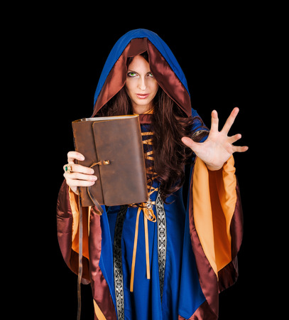 spells: Beautiful young halloween witch wearing vintage gothic dress with hood holding magical book of spells in old leather cover making magic isolated on black background