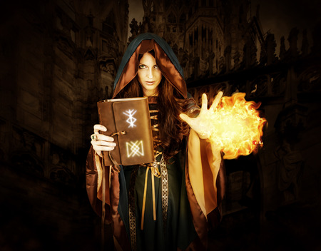 spells: Beautiful young halloween witch wearing vintage gothic dress with hood holding magical book of spells in old leather cover with runes making fire ball magic in dark gothic castle Stock Photo