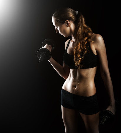 woman black background: Dark contrast photo of young beautiful fitness woman with beads of sweat which training in gym. Working out with dumbbells on black background