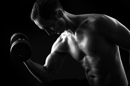 man working out: Dark contrast black and white silhouette of young muscular fitness man. Bodybuilder with beads of sweat training in gym. Working out with dumbbells on black background
