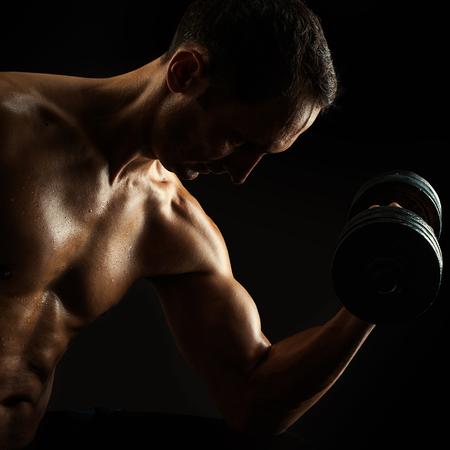 adentro y afuera: Contraste brutal silueta oscura de hombre joven de fitness muscular. Fisicoculturista con los granos de la formación de sudor en el gimnasio. Hacer ejercicio con pesas en el fondo negro Foto de archivo