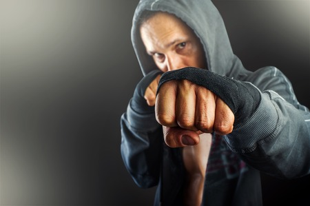 patada: puño del joven hombre peligroso primer. hombre atlético que lleva graves fuertes camisetas sudadera con capucha de pie en actitud del boxeo