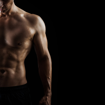 nude stomach: Close up view of very muscular handsome sexy guy isolated on black background, naked torso