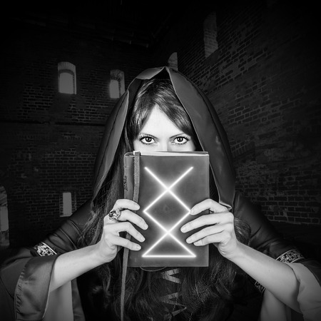 spells: Beautiful young halloween witch wearing vintage gothic dress with hood holding magical book of spells in old leather cover inside ancient dark castle. Black and white