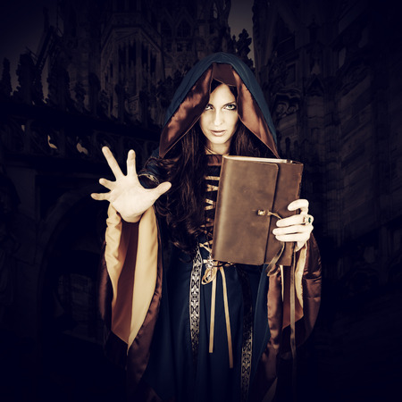 spells: Beautiful young halloween witch wearing vintage gothic dress with hood holding magical book of spells in old leather cover making magic isolated on white background Stock Photo