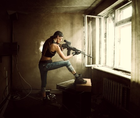 soldiers: Young beautiful woman sniper and Soldier aiming a rifle at the window. She is in old room of abandoned building
