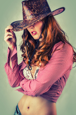 sexy cowboy: Beautiful cowgirl style woman wearing cowboy hat, studio shot