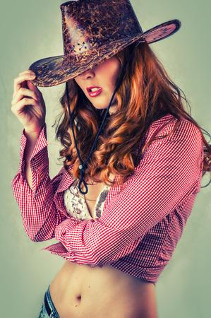 vaqueritas: Mujer del estilo de vaquera hermosa que desgasta el sombrero de vaquero, tiro del estudio