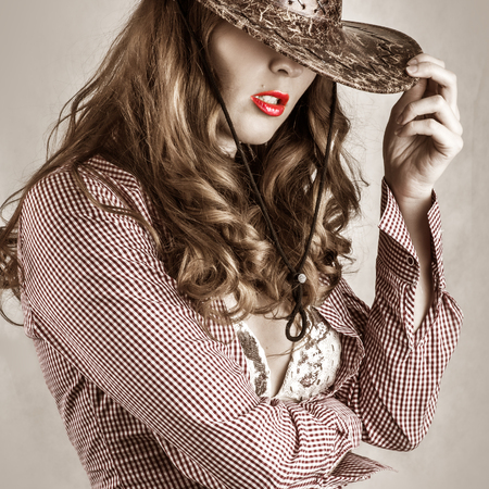rodeo cowgirl: Beautiful cowgirl style woman wearing cowboy hat, studio shot
