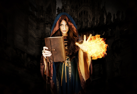 Beautiful young halloween witch wearing vintage gothic hood holding magical book of spells in old leather cover making fire ball magic near dark gothic castle