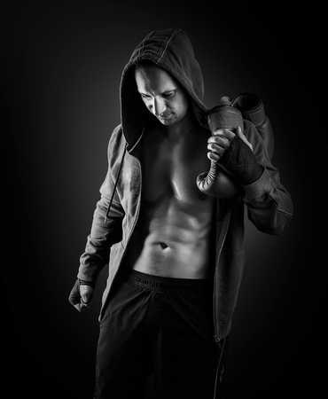 boxing: Young muscular men boxer wearing jacket with hood. Boxing gloves slung over his shoulder on black background. Black and white. Stock Photo