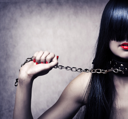 female hand: Fashion portrait of young beautiful female model. Glamour woman with long black hair and sexy hairstyle. Lady with leather collar with studs on a metal chain in hand