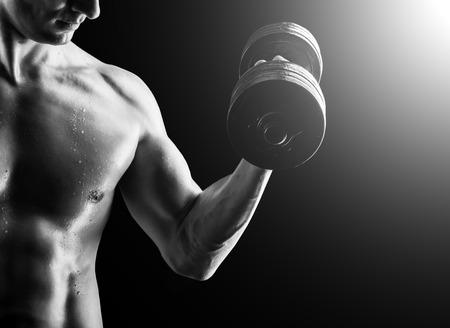 fitness hombres: Concéntrese en el estómago. Oscuro tiro contraste de joven musculoso estómago del hombre de la aptitud y el brazo. Fisicoculturista con los granos de la formación de sudor en el gimnasio. Hacer ejercicio con pesas en el fondo negro Foto de archivo
