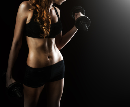 triceps: Dark contrast photo of young beautiful fitness woman with beads of sweat which training in gym. Working out with dumbbells on black background