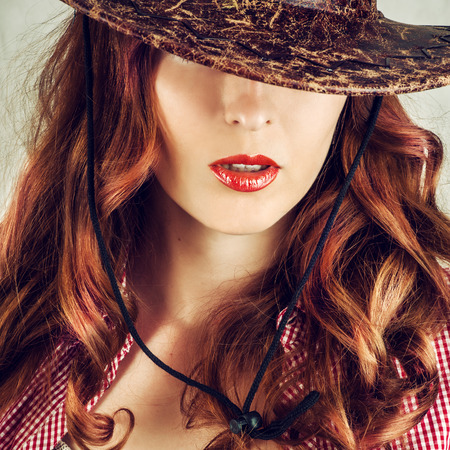 full red: Beautiful full red lips. Part of face of young beautiful woman covered by cowboy hat