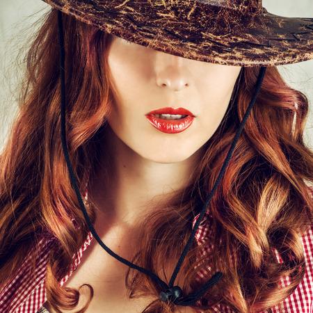 full red: Belle labbra rosse piene. Parte del fronte di giovane bella donna coperto da cappello da cowboy