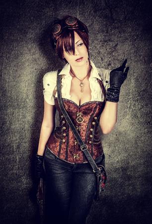 flintlock pistol: Portrait of a beautiful steampunk woman wearing vintage corset and retro goggles Stock Photo