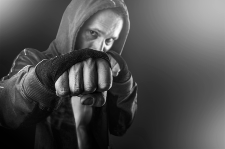 dangerous: Black and white fist of young dangerous man closeup. strong serious  athletic man wearing hoodie shirts standing in boxing pose