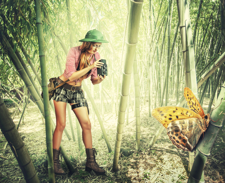 naturalist: Young retro styled woman traveler in tropics holding vintage camera  photographed Big tropical butterfly