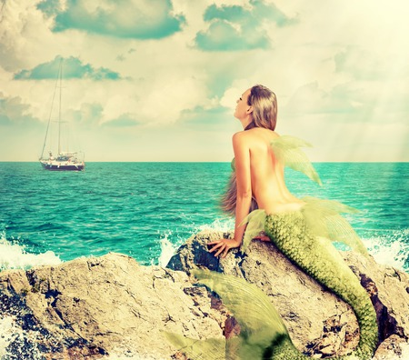 Beautiful Mermaid with fish tail sitting on rocks and looks at a ship on the horizon