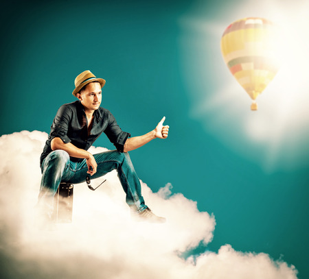 hitch: Young handsome man traveller sitting on a clouds with a sign hitch hiking Stock Photo