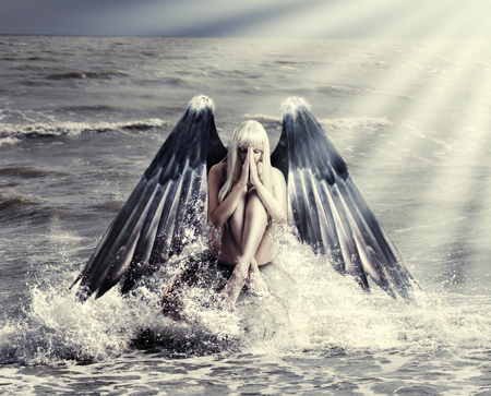 Fantasy portrait of woman with dark angel wings praying while sitting in  spray of  sea during storm