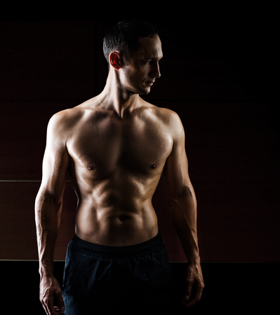 Close up view of very muscular handsome sexy man isolated on black background, naked torso
