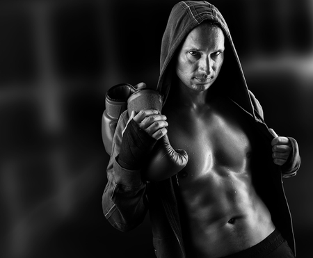 white man: Dangerous Young muscular man boxer wearing jacket with hood. Boxing gloves slung over his shoulder on dark background indoor. Black and white Stock Photo