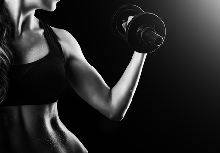 Black and white dark contrast photo of muscular arms, waist and belly with beads of sweat of young fitness woman, which training, working out with dumbbells on black background Standard-Bild