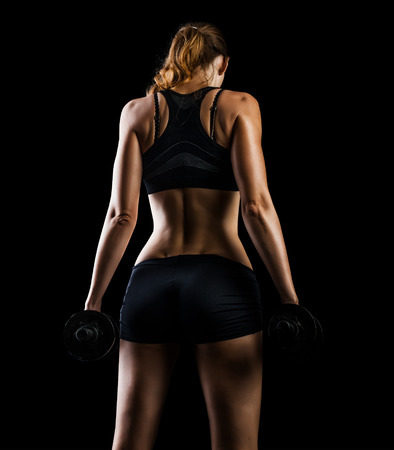 dumbbell: Dark contrast photo of back side of young beautiful fitness woman with beads of sweat which training in gym. Working out with dumbbells on black background