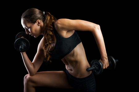 female hands: Dark contrast shot of young beautiful fitness woman with beads of sweat which training in gym. Working out with dumbbells on black background Stock Photo