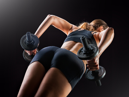 Focus on black shorts. Dark contrast image of fitness womans back and buttocks. She is training - doing squats with dumbbells on black background in studio.