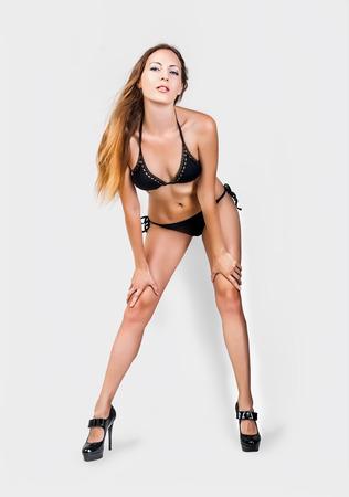 belles jambes: Beau modèle femme mince avec de longues jambes et corps parfait mini bikini noir sur fond gris clair en studio