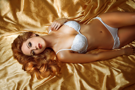 Amazing and beautiful woman lingerie model is on a golden silk bed in bedroom Stock Photo