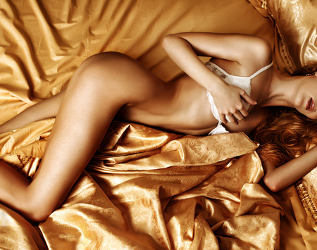 Dar contrast photo of amazing and beautiful woman lingerie model is on a golden silk bed in bedroom
