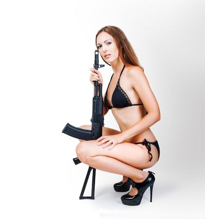 airsoft gun: Beautiful sexy blonde girl in bikini holding airsoft gun (rifle) sitting in studio on white background