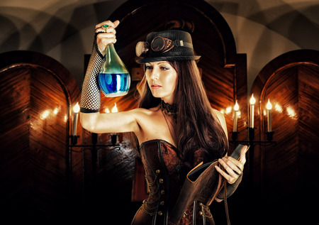 spells: alchemist. Beautiful brunett girl witch wearing steampunk style prepares a potion or poison in a secret occult lab and reads a magical book of spells