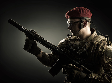 guerilla warfare: silhouette of Young handsome military man in italian camouflage holding automatic rifle, he wearing red beret and gloves Stock Photo