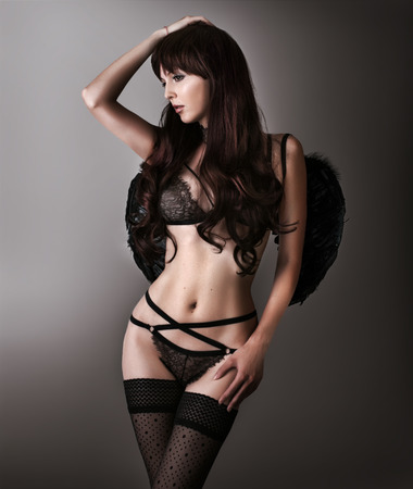skimpy: Fashion studio shot of beautiful slim young woman model wearing black lace lingerie - bra, panties, stockings and angel wings on black background Stock Photo
