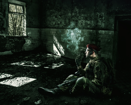 weary: war. weary soldier wearing military uniform with automatic riffle  sitting at night in the destroyed building Stock Photo