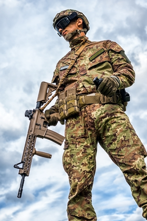 Young handsome military man holding automatic rifle and hand grenade on sky background. Airsoft Stock Photo