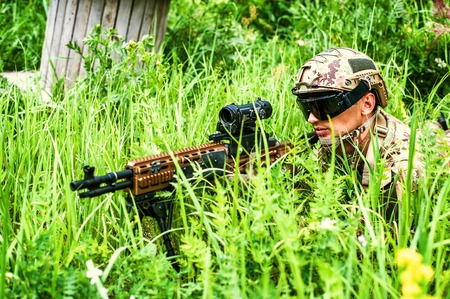 lies: Military man sniper with automatic rifle with a telescopic sight lies in grass in forest. Airsoft