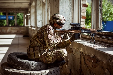 aiming: Military man sniper with automatic rifle with a telescopic sight sitting by the window in building